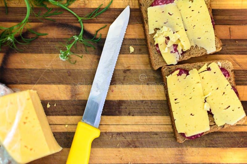 Hakbord met mes, sandwich en greens stock afbeelding