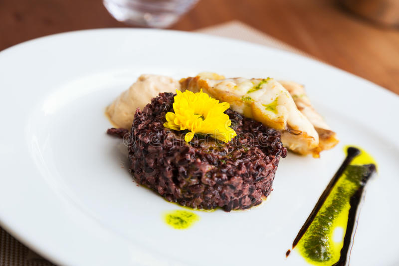 Hake with black rice and sauce stock image