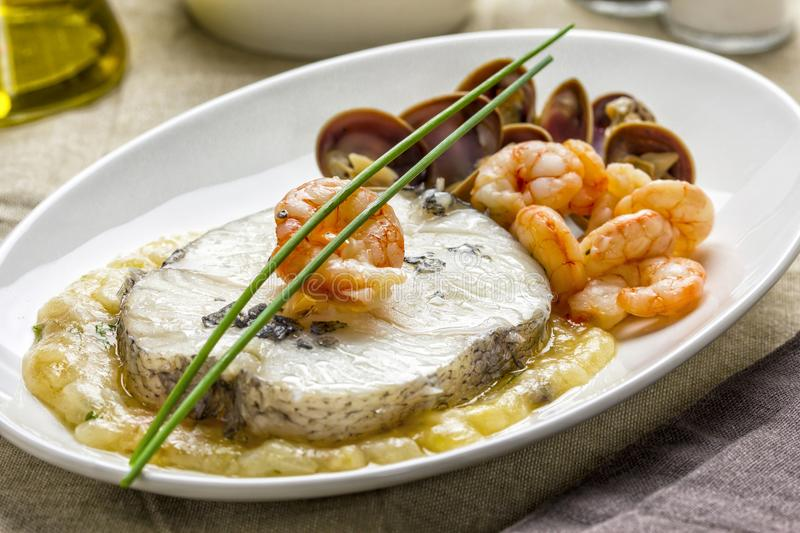 Hake dish with clams and prawns stock photography