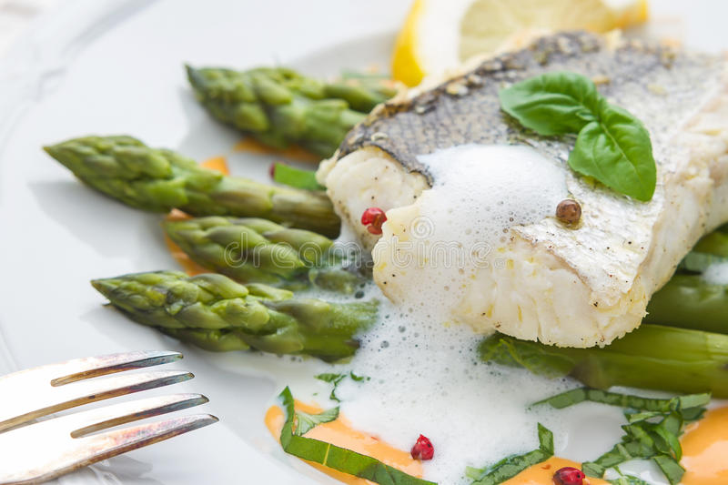 Hake fillet with green asparagus foam sauce royalty free stock photo