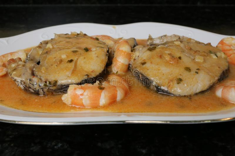 Hake fillets in prawns sauce a fish dish. The fillets of hake in prawns sauce is a very typical fish dish. The slices of fish are in a white plate on a black stock photography