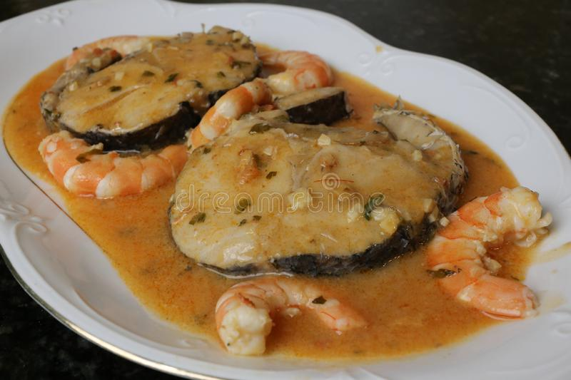 Hake fillets in prawns sauce a fish dish. The fillets of hake in prawns sauce is a very typical fish dish. The slices of fish are in a white plate on a black stock image