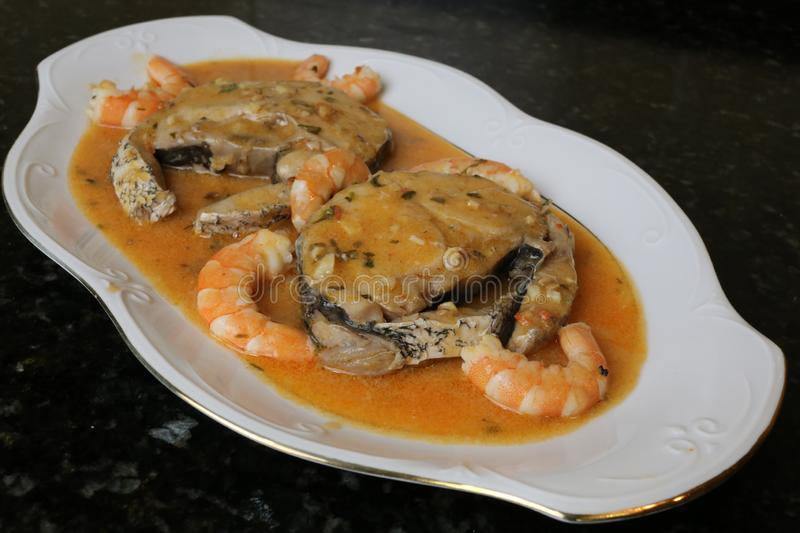Hake fillets in prawns sauce a fish dish. The fillets of hake in prawns sauce is a very typical fish dish. The slices of fish are in a white plate on a black royalty free stock images