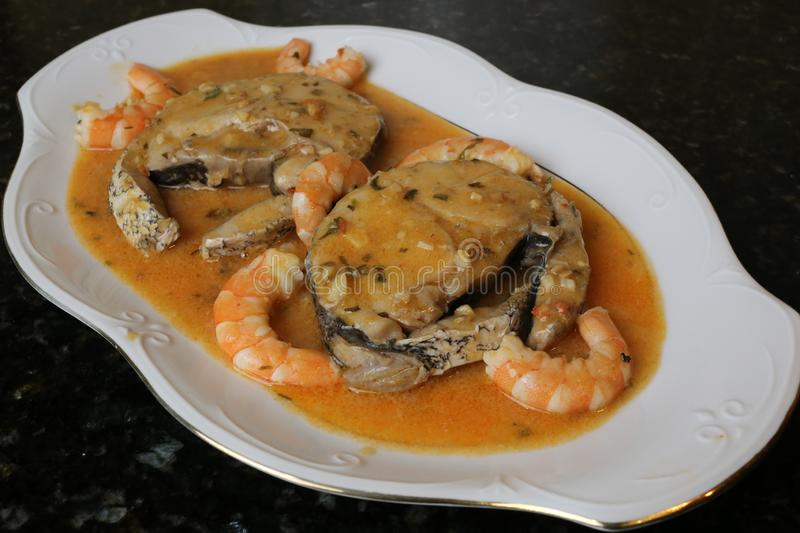 Hake fillets in prawns sauce a fish dish. The fillets of hake in prawns sauce is a very typical fish dish. The slices of fish are in a white plate on a black royalty free stock photo
