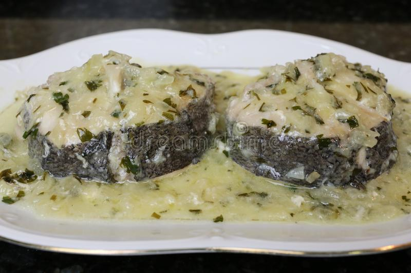 Hake in green sauce a very popular fish dish. Hake in green sauce is a very popular fish dish in the kitchen. The fish is in a white plate on a black background royalty free stock photos