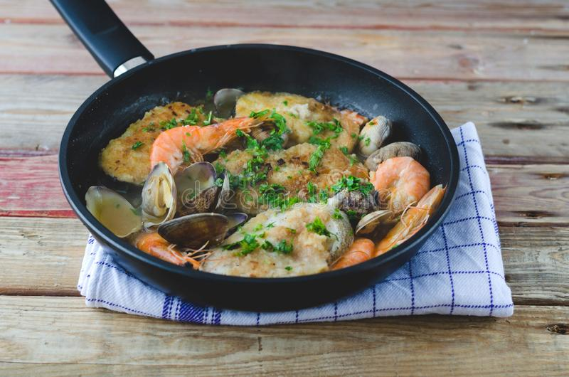 Hake with prawns and clams in frying pan. stock photography