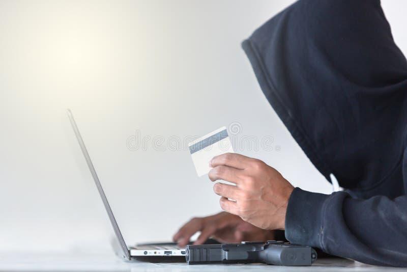 Hakker die aan een code en stealing creditcard, mens werken die a dragen royalty-vrije stock fotografie