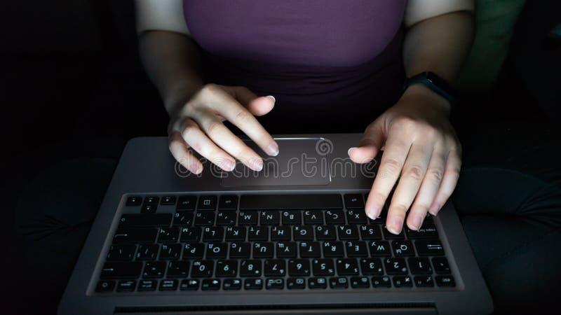 Hakker die laptop met behulp van handen die op PC laat bij nacht, mening hierboven typen van Onherkenbaar meisje, die in een donk stock fotografie