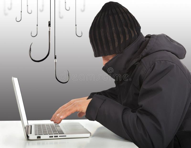 Hakker die met een laptop computer en haken werken stock afbeeldingen