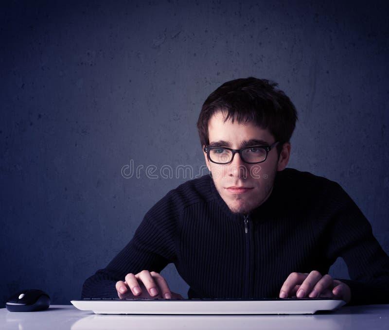 Hakker die met toetsenbord aan blauwe achtergrond werken stock foto