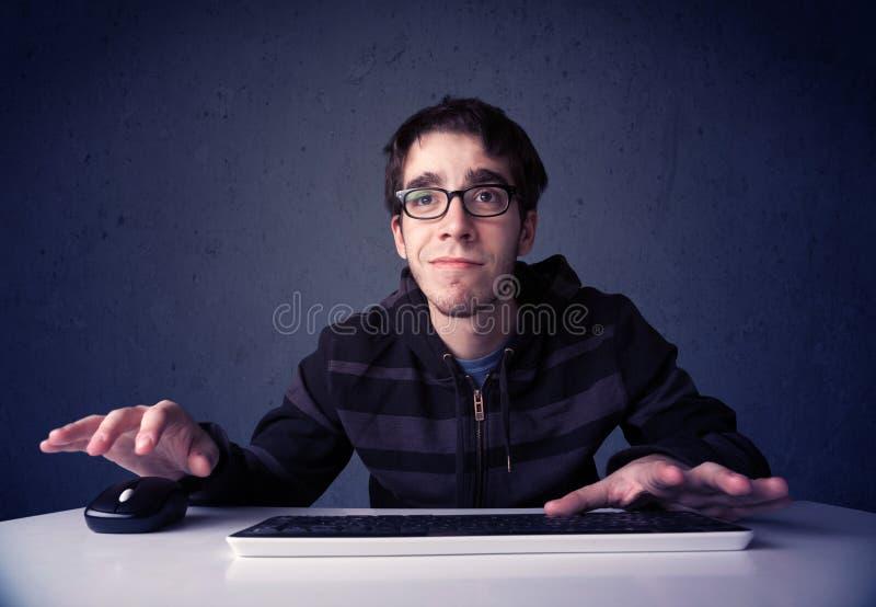 Hakker die met toetsenbord aan blauwe achtergrond werken stock afbeelding