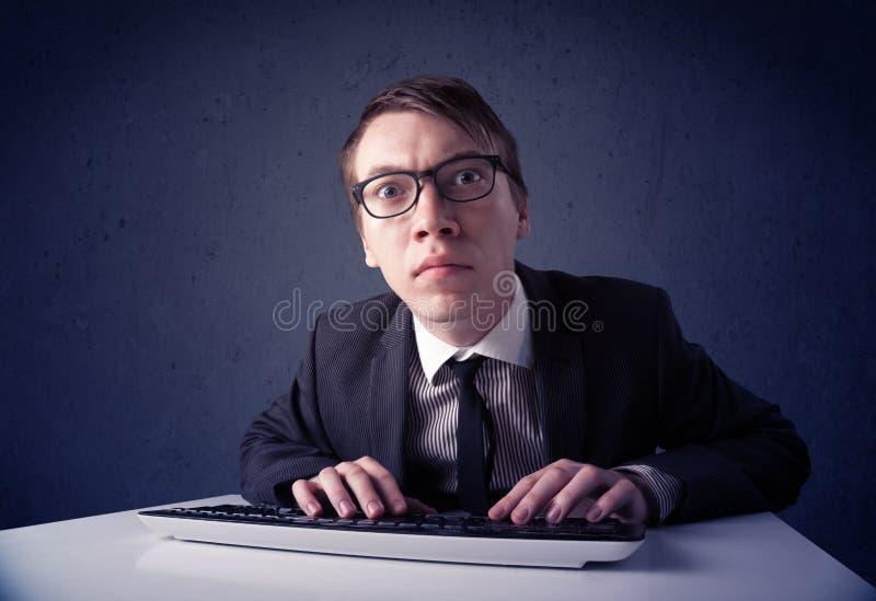 Hakker die met toetsenbord aan blauwe achtergrond werken stock foto's