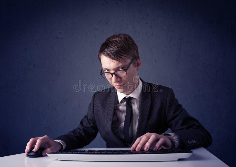 Hakker die met toetsenbord aan blauwe achtergrond werkt stock foto's