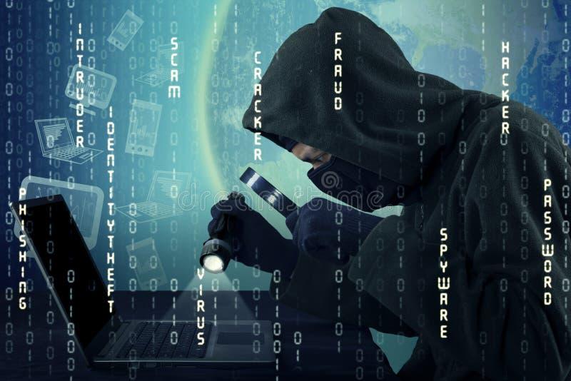 Hakker die notitieboekjecomputer met behulp van om informatie te stelen royalty-vrije stock afbeelding