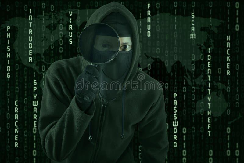 Hakker die vergrootglas voor het spioneren met behulp van royalty-vrije stock afbeelding