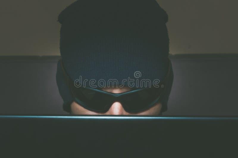 Hakker die vertrouwelijke informatie over zijn computer binnendringen in een beveiligd computersysteem terwijl hij hoed en zonneb stock foto's