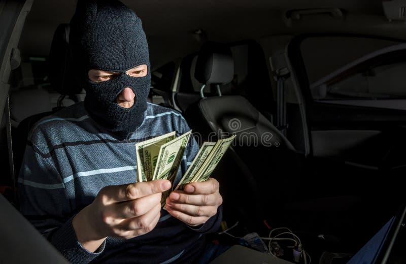 Hakker met laptop binnen een auto stock afbeelding