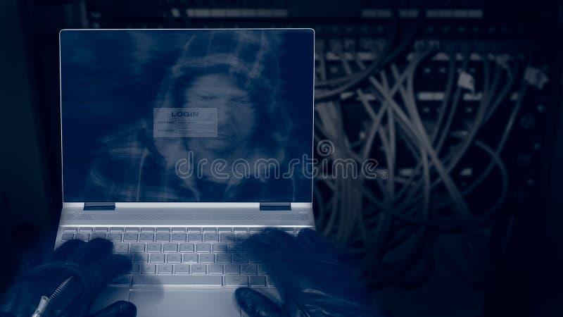 Hakker met laptop op een donkere achtergrond van gestructureerde aanleg van kabelnetten royalty-vrije stock foto