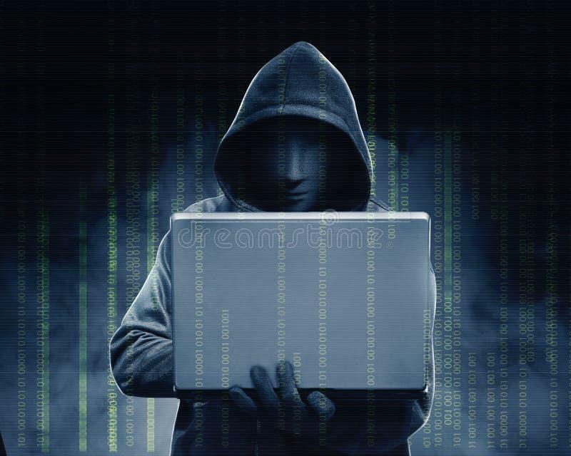 Hakker in zwarte laptop van de hoodieholding met zijn hand en binaire code stock afbeelding