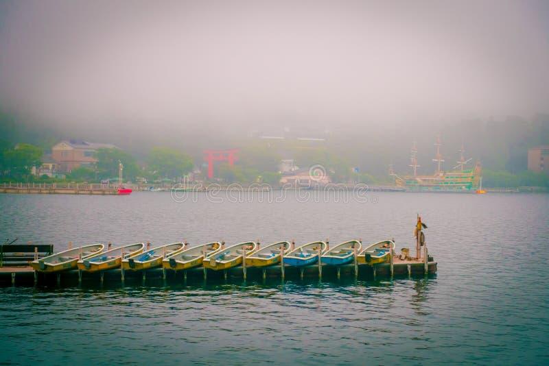 HAKONE, GIAPPONE - 2 LUGLIO 2017: I pescherecci ed il portone rosso di Torii di Hakone shrine sul lago Ashi il giorno nebbioso fotografie stock libere da diritti