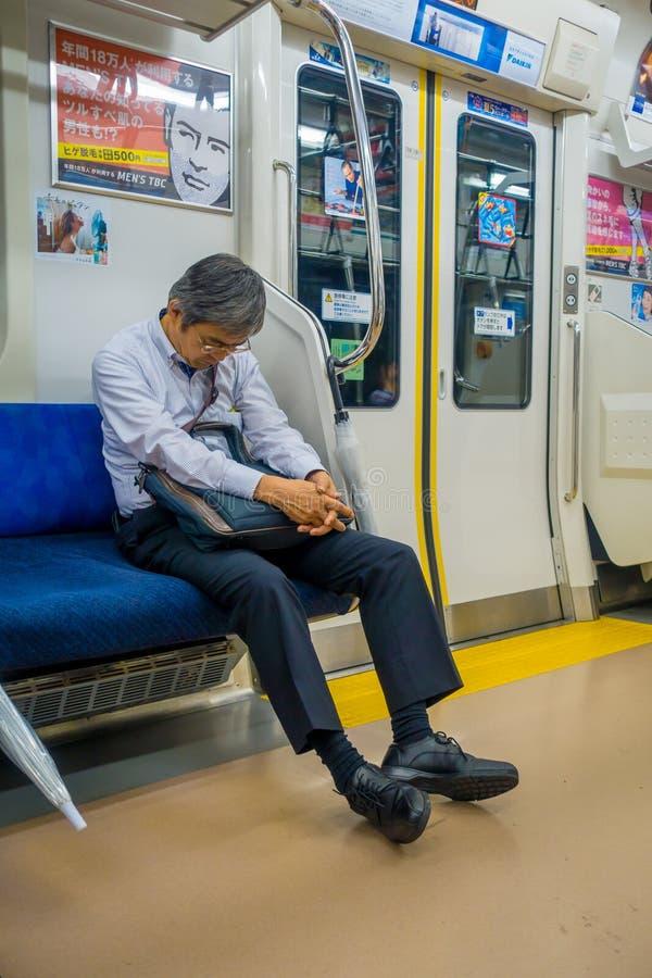 HAKONE, JAPÓN - 2 DE JULIO DE 2017: Hombre no identificado que duerme en el interior del tren durante día lluvioso y nublado imagenes de archivo