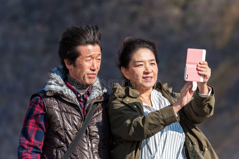 HAKONE, JAPÓN - 5 DE NOVIEMBRE DE 2017: El par japonés hace selfies Con el foco selectivo imagen de archivo libre de regalías