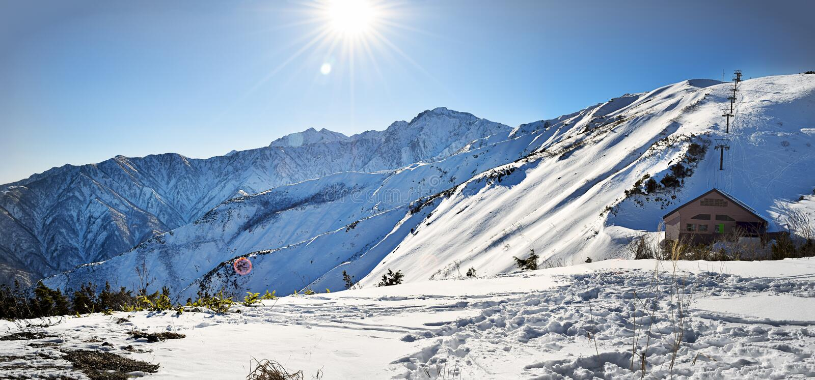 Hakuba mountain range on a sunny day. Hakuba mountain range in the afternoon on a clear sunny day. The very steep area directly beneath the sunshine is between royalty free stock photo