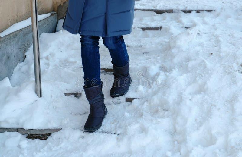 Hal trappa Closeupkvinnas ben i en blått ner omslaget som går ner en snöig trappuppgång royaltyfria bilder