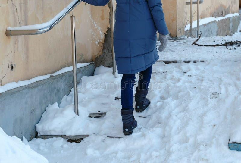 Hal trappa Oigenkännlig kvinna i en blått ner omslaget som går upp en snöig trappuppgång arkivfoton