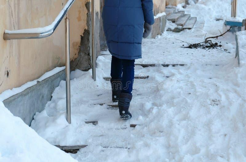 Hal trappa Oigenkännlig kvinna i en blått ner omslaget som går upp en snöig trappuppgång arkivfoto