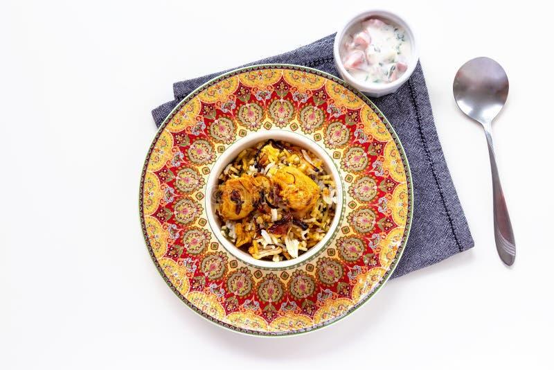 Halal India?ski kurczak Biryani s?uzy? z jogurtu pomidorowym raita nad bia?ym t?em Selekcyjna ostro?? obraz royalty free