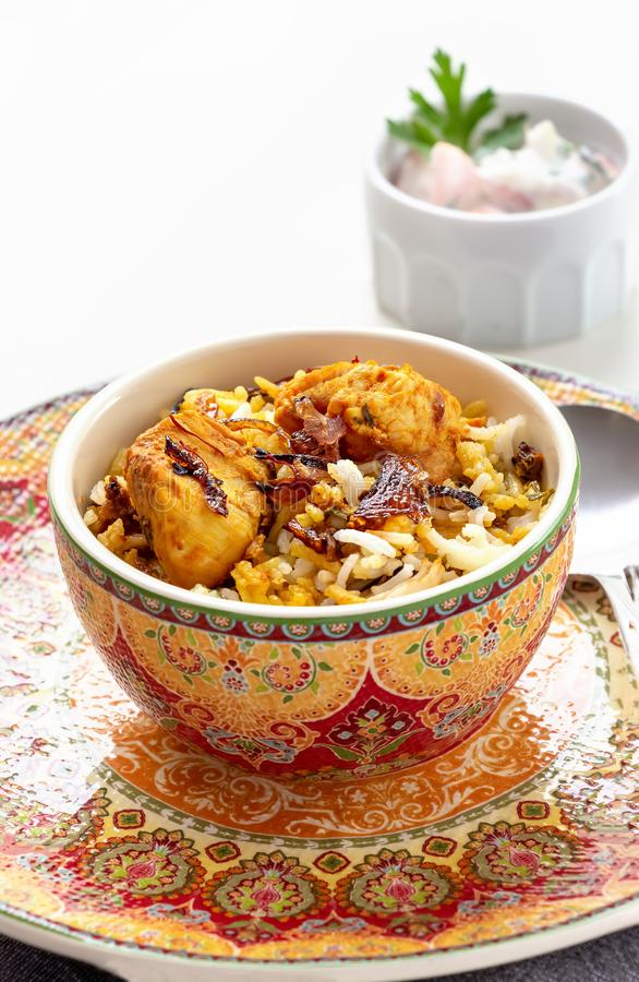 Halal Indian chicken Biryani served with yogurt tomato raita over white background. Selective focus stock images