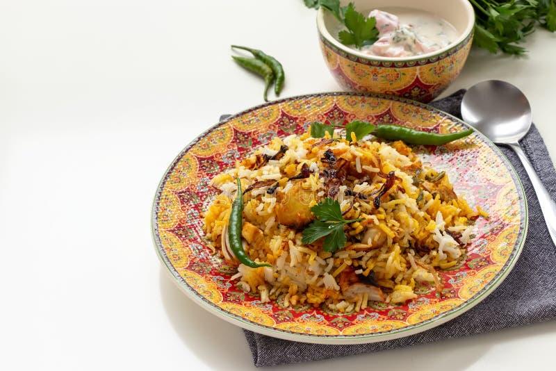 Halal Indian chicken Biryani served with yogurt tomato raita over white background. Selective focus.  stock image