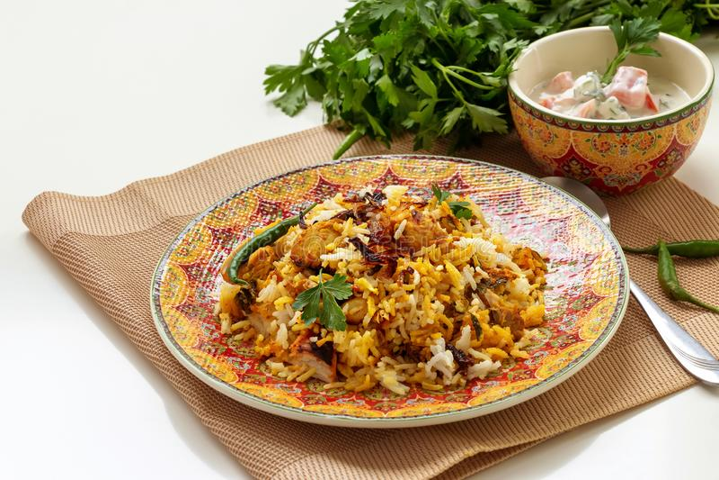 Halal Indian chicken Biryani served with yogurt tomato raita over white background. Selective focus.  royalty free stock photo
