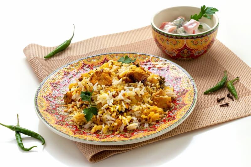 Halal Indian chicken Biryani served with yogurt tomato raita over white background. Selective focus.  stock photo