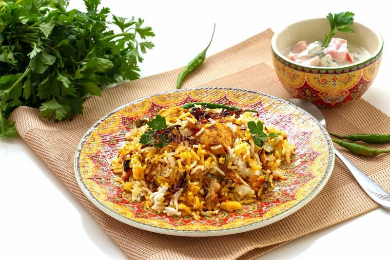 Halal Indian chicken Biryani served with yogurt tomato raita over white background. Selective focus.  stock images