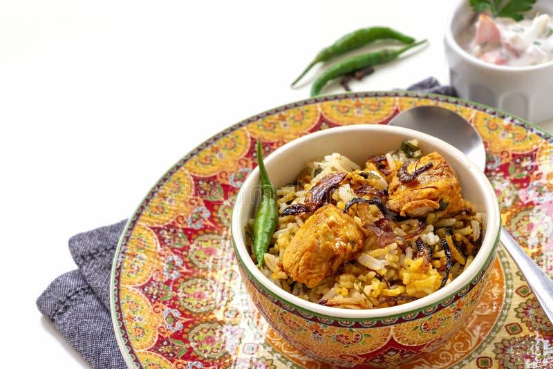 Halal Indian chicken Biryani served with yogurt tomato raita over white background. Selective focus.  royalty free stock photos