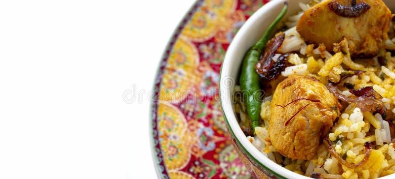 Halal Indian chicken Biryani served with yogurt tomato raita over white background. Selective focus. Banner size. Top view royalty free stock photos