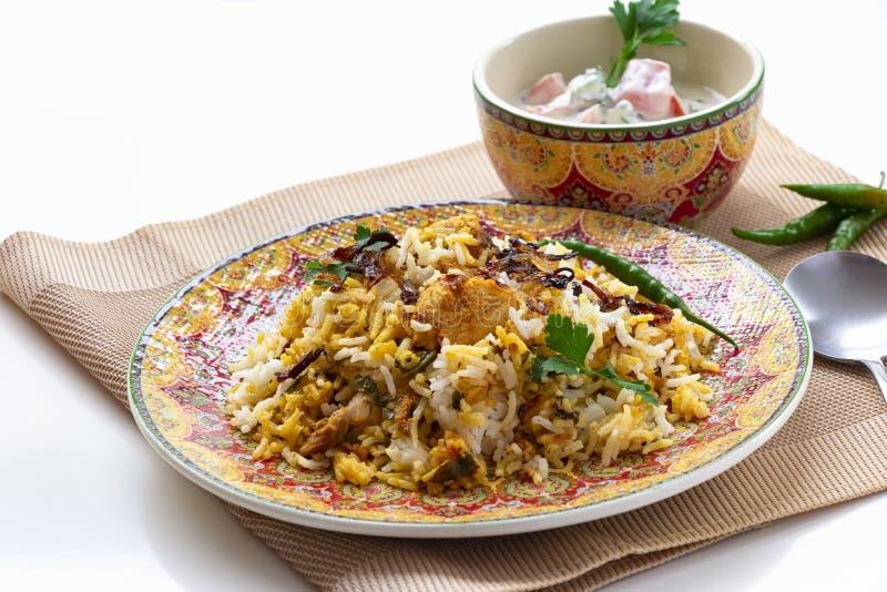 Halal Indian chicken Biryani served with yogurt tomato raita over white background. Selective focus.  royalty free stock photography