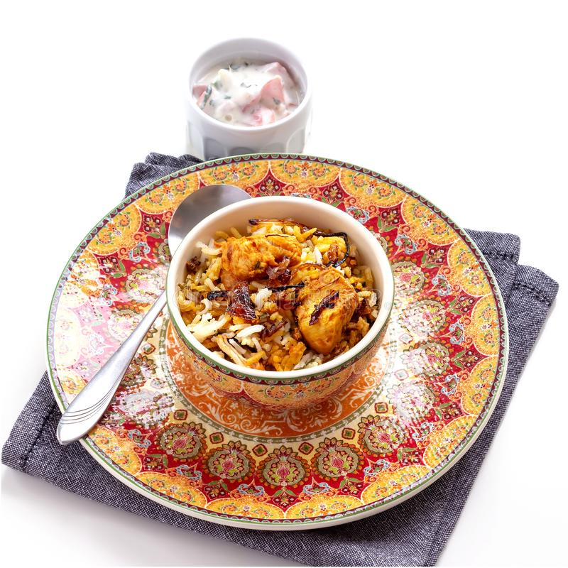 Halal Indian chicken Biryani served with yogurt tomato raita over white background. Selective focus. Square photo royalty free stock image