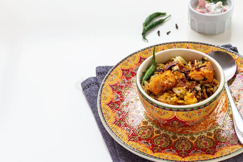 Halal Indian chicken Biryani served with yogurt tomato raita over white background. Selective focus.  stock photography