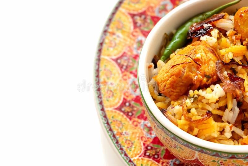 Halal Indian chicken Biryani served with yogurt tomato raita over white background. Selective focus. Top view stock photo