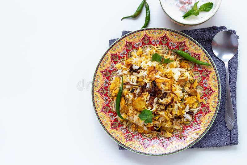 Halal Indian chicken Biryani served with yogurt tomato raita over white background. Selective focus. Top view royalty free stock images