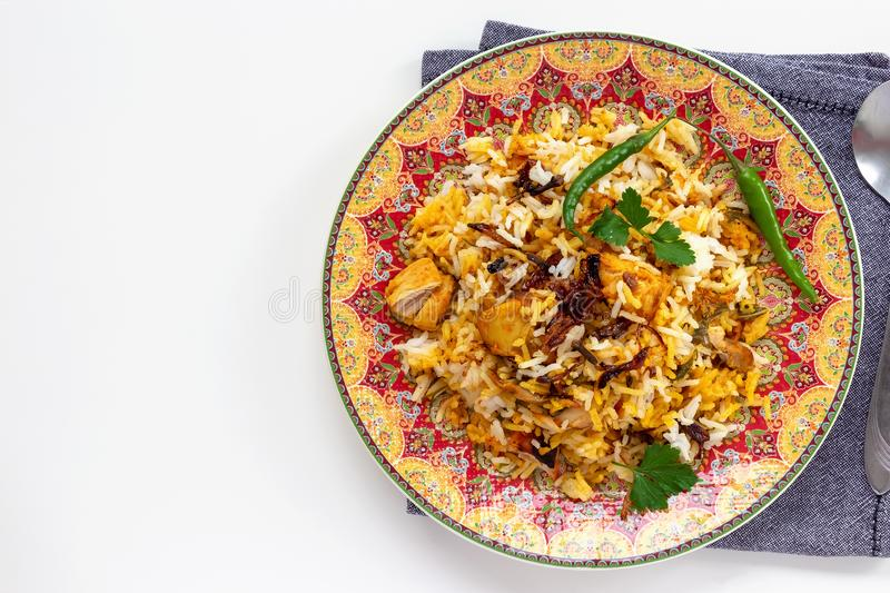 Halal Indian chicken Biryani served with yogurt tomato raita over white background. Selective focus. Top view.  royalty free stock images