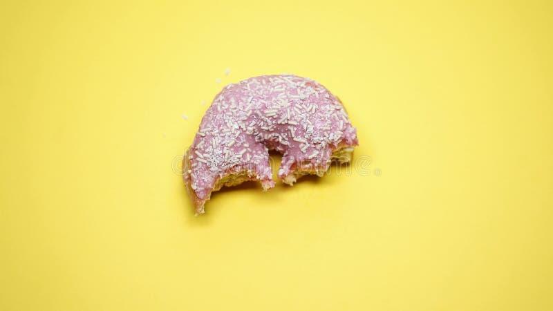 Halb aufgegessener Donut auf gelbem Hintergrund, ungesunder Fertigkost und ungesunder Diät, Makroschuß stockfotografie