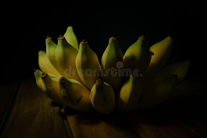 Halb fertige Bananenfrucht auf schwarzem Hintergrund lizenzfreie stockfotos