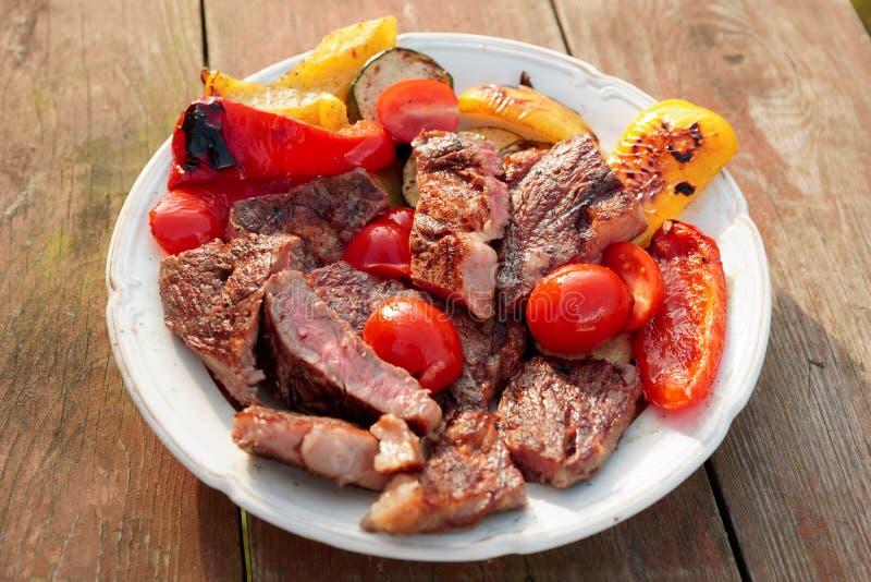 Halb gares gebratenes Steak mit Gemüse auf Platte stockfotos