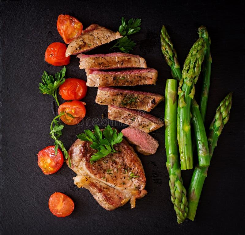 Halb gares Rindfleisch des saftigen Steaks mit Gewürzen und Spargel lizenzfreie stockfotos