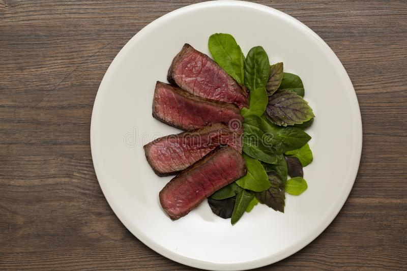 Halb gares Rindfleisch des saftigen Steaks mit grünem Salat und Tomaten stockfotografie