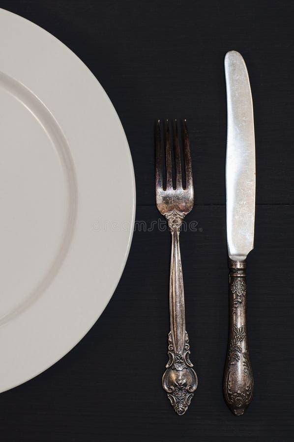 Halb leere weiße Platten, Weinlesemesser und Gabel auf Tabelle lizenzfreie stockbilder